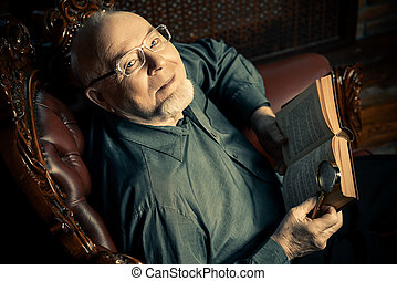 retro style portrait - An old intelligent man reading a book...
