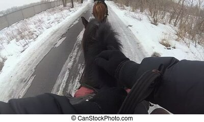 Riding a horse in winter. First person view, top view -...