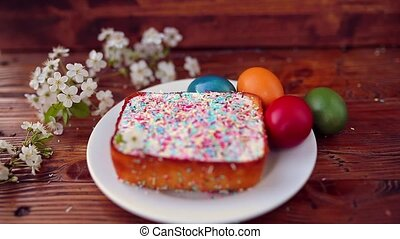 Easter cake on a plate, on a wooden board. The painted eggs...