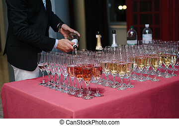 waiter pours the champagne into the glasses at the buffet...