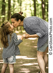 Mother and young daughter walk in the woods - young Mother...