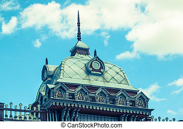 Roof of an ancient building with elements of wood carving on the sky background.