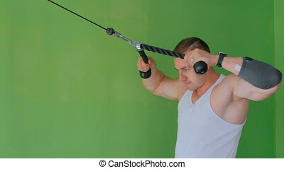 Athletic young man working out on fitness exercise equipment...