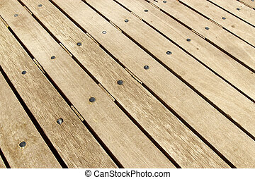 Weathered large wooden decking planks close up.