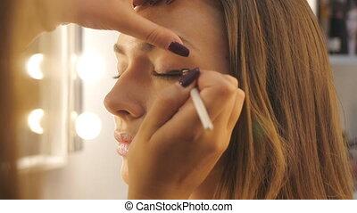 Makeup artist backstage. Closeup shot of makeup woman's...