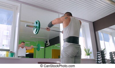 Athletic young man doing exercises with barbell at gym,...