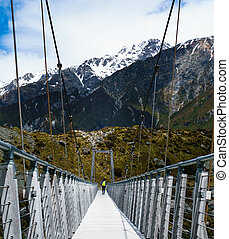 Hiker Walking Across Bridge with Mountain in the Background...