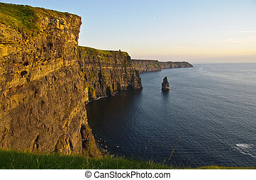 sunset over famous cliffs of moher county clare, ireland