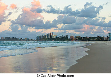 Beach view at sunset - Beach view with soft waves and urban...