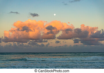 Beautiful ocean with colorful sky at sunset with full moon...