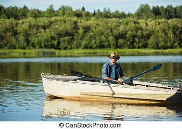 Man in a rowing boat. - A man in a cowboy hat and sunglasses...
