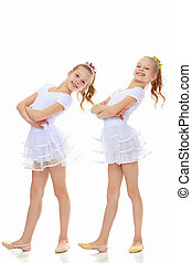 2 girls gymnast in white suits. - 2 cheerful girls twins in...