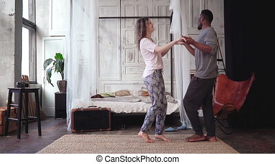 Happy multiethnic couple in pajamas dancing together. Maw...