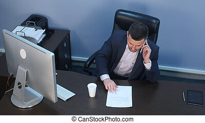Businessman talking on phone and working on computer in...