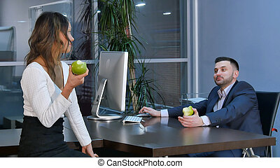 Two office workers having a break, aeting green apples and...