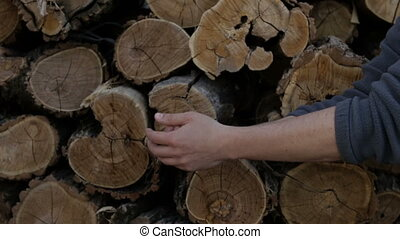 A man washes his hands on the background of cut logs - A man...