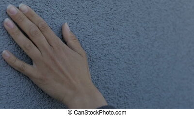 Female hand gently strokes the texture wall - A female hand...