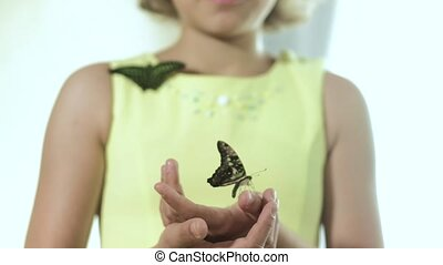 Girl holding a butterfly in her arms