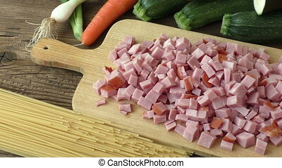 Pieces of chopped ham on wooden plate