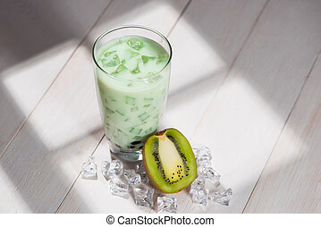 Bubble tea. Homemade Kiwi Milk Tea with Pearls on wooden table.