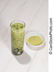 Boba / Bubble tea. Homemade Matcha Milk Tea with Pearls on wooden table.