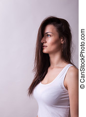 Portrait of woman wearing a white shirt on gray background....
