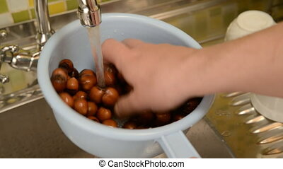 Wash the nuts in the colander in the kitchen. - Nut...