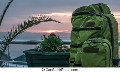 Backpacks of different sizes stand near the sea at sunrise...