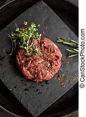 Raw ground beef meat steak cutlets with herbs and spices on...