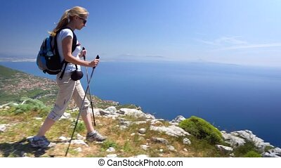 Young woman hiking in mountains over Amalfi coast in Italy
