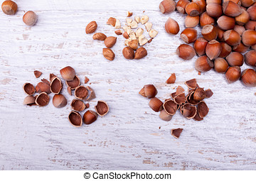 Over top view of Hazelnuts on white wooden background in...