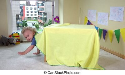 Cute girl hiding under table covered with wrap at home