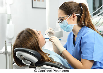 Dentist examining a patient teeth - Dentist wearing...