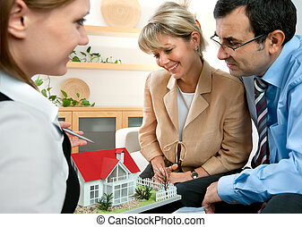 discussing with real estate agent - Couple discussing with...