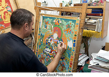 The artist paints a Buddhist icon - The artist sitting...