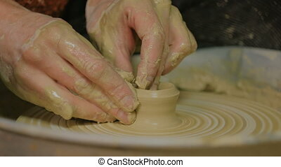 Professional male potter making ceramics in workshop -...