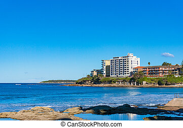 High waves and waterfront buildings on sunny day - Cronulla...