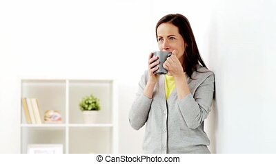 happy woman drinking tea or coffee at home - people, drinks...
