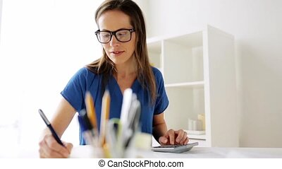 woman with calculator and notebook at office - business,...