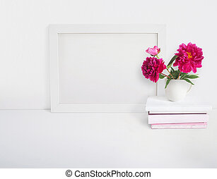 White blank wooden frame mockup with a peony flowers bouquet in a porcelain cup and pile of books lying on the table. Poster product design. Styled stock feminine photography. Home decor.