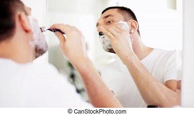man shaving beard with safety razor at bathroom - beauty,...