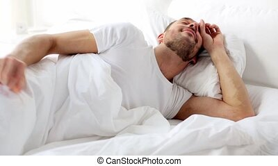 man waking up in bed at home - rest, sleeping and people...