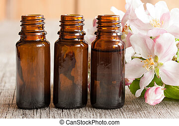 Three bottles of essential oil with apple blossoms