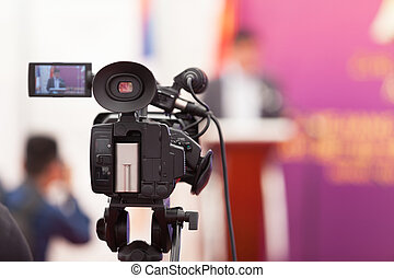 Filming an media event with a video camera - Video camera on...