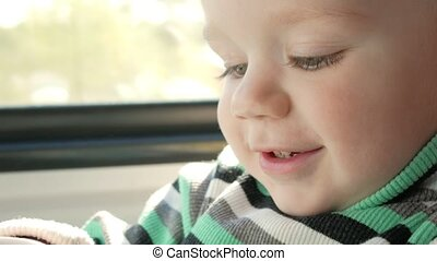 The little boy is riding in a moving train near the window. He smiles and looks at the book. Close-up