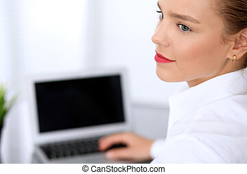 Business woman is typing on laptop computer