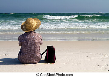 Woman Sitting On Beach With Bag - Mature woman sits on the...