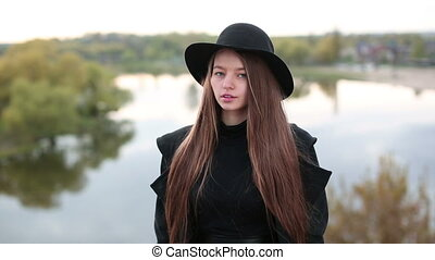 Young beautiful fashionable woman in hat posing on blurry nature background