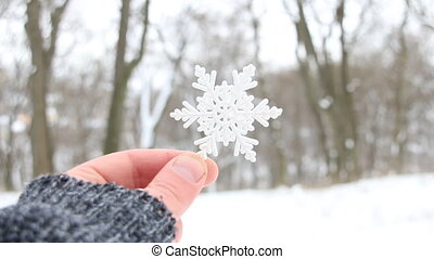 snowy creative concept, hand holding a snowflake on a...
