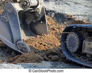 road construction in a city with a shovel digging up the...